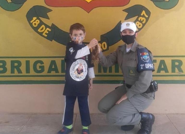 Menino doa cabelo para campanha da Brigada Militar em São Borja
